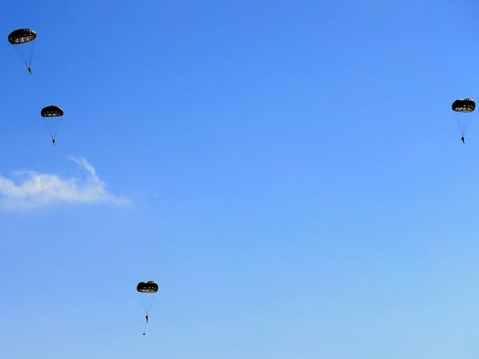 Members of the 181st Special Operations Weather Team parachute from a UH-60 Blackhawk during a training exercise as they conduct a deliberate static line personnel parachute drop into Corpus Bay on Friday, July 28, 2017, at the USS Lexington Museum on the Bay in Corpus Christi.