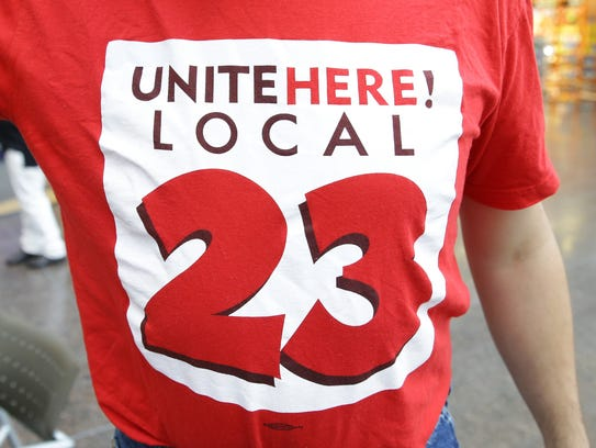Benjamin Calbert shows off his union shirt at Indianapolis International Airport, where some workers are seeking a minimum wage of at least $13 an hour.