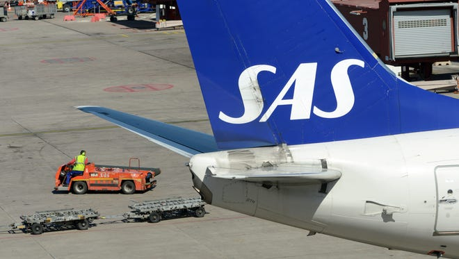 This file photo from May 3, 2012, shows a baggage belt truck passing behind the tail of one of SAS's Boeing 737 aircraft at the Stockholm Arlanda Airport.