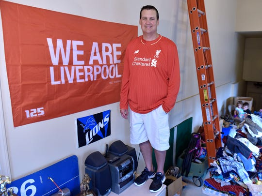 Neal Ruhl, 40, of Washington Township, poses next to a Liverpool FC flag that hangs on the wall in his garage.