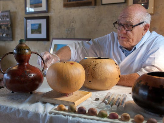 """In a photo from June 13, 2015, Doug Wolff shows off some of his artistic gourds and paintings that are displayed at the EastEnd Studio and Gallery in downtown Marshall, Mich. Since his retirement as director of Dam Site Design, a design consultant firm in Ceresco, Wolff has found art, both as an acrylic painter and, perhaps most noteworthy, as a gourd carver. His exhibition is titled ?The Wonders of Wolff."""" (Seth Graves/Battle Creek Enquirer via AP)"""
