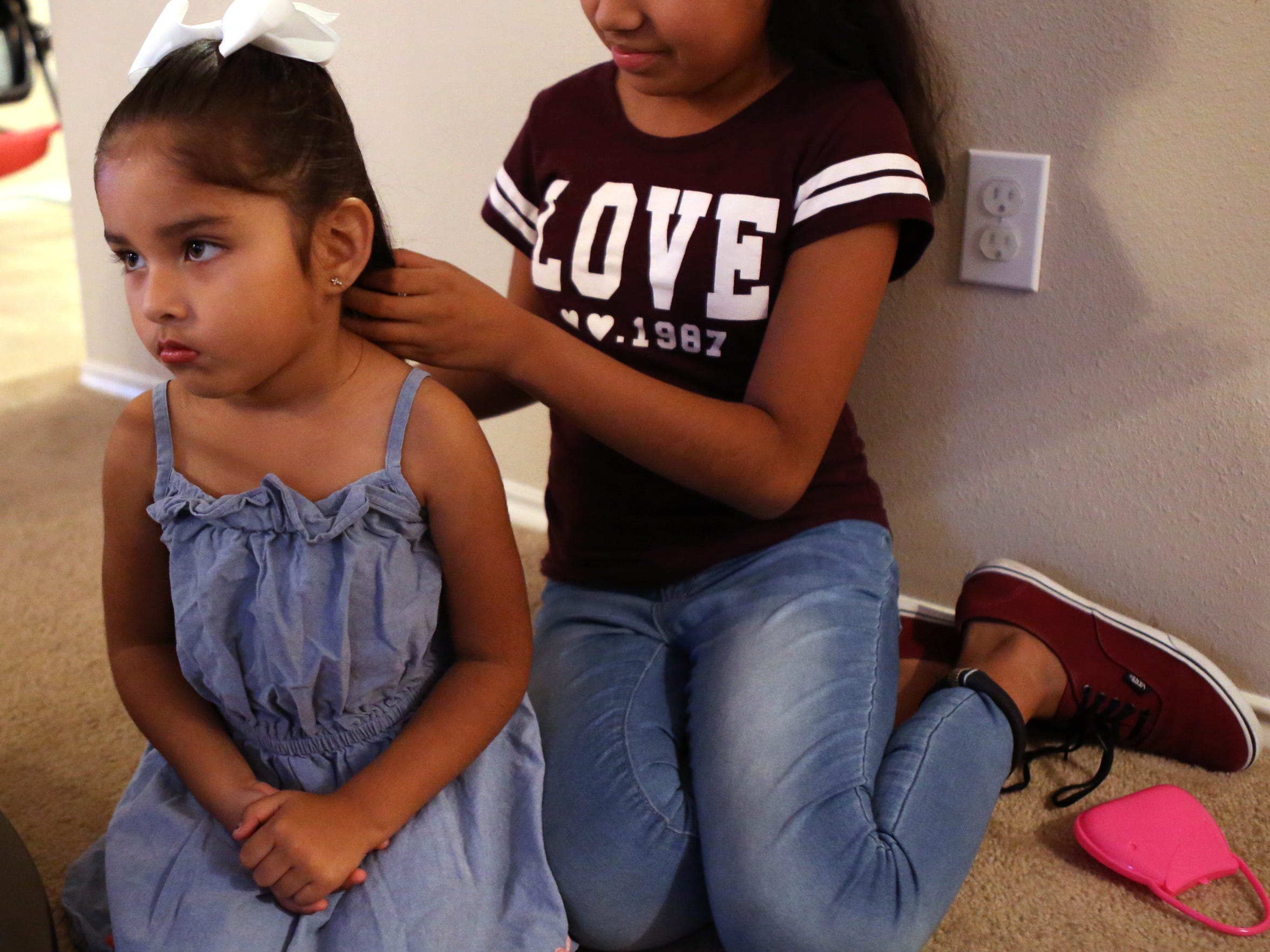 Evalynn Rojas, 4, gets her hair done by her aunt, Alejandra Rojas, 12, while visiting with family on Nov. 2, 2017. Evalynn, who is a U.S. citizen, is the daughter of former DACA recipient Ezequiel Rojas Martinez, who is seeking legal permanent residency.