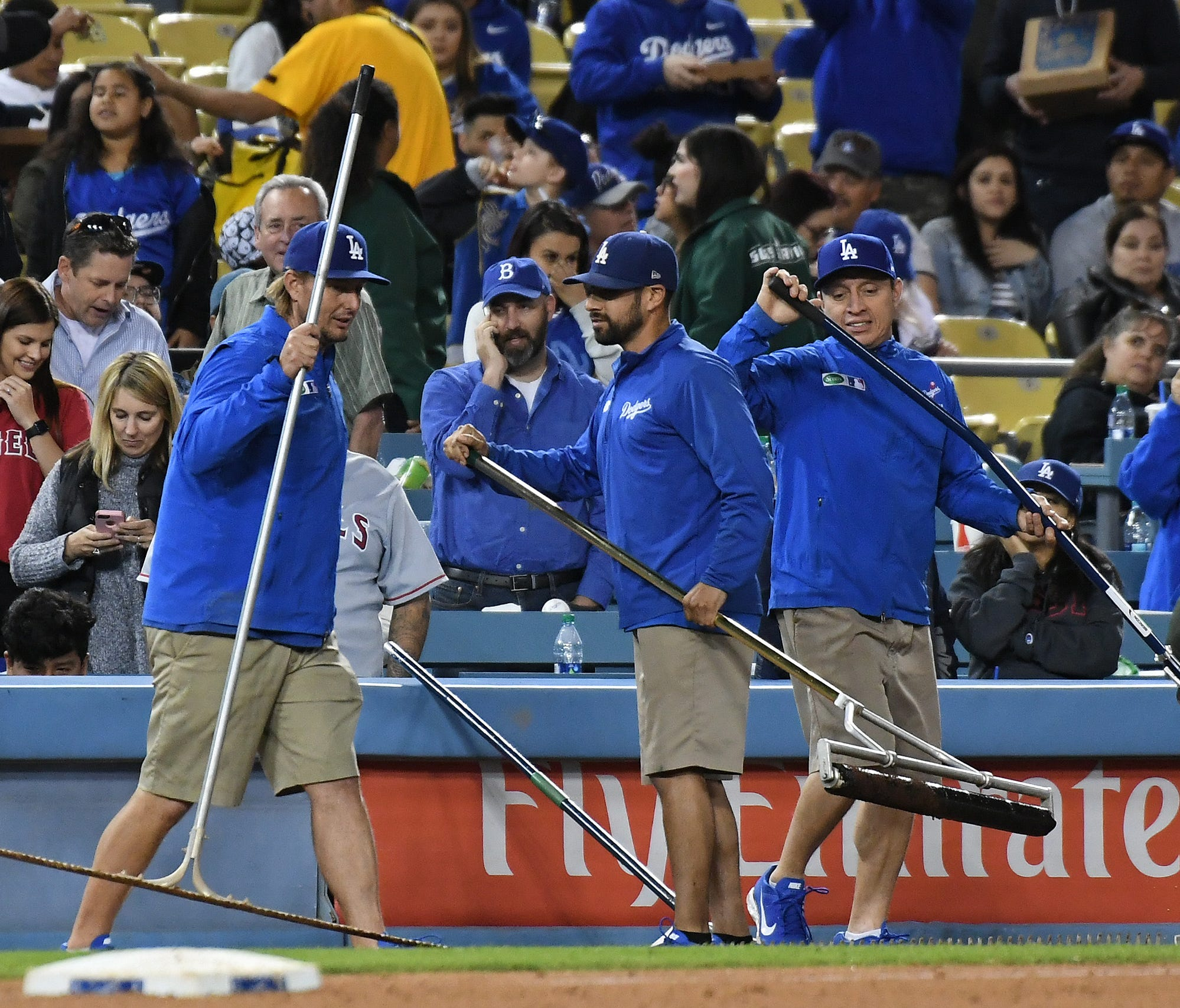 Groundskeepers sweep water on the field during the fifth inning of an exhibition game at Dodger Stadium.