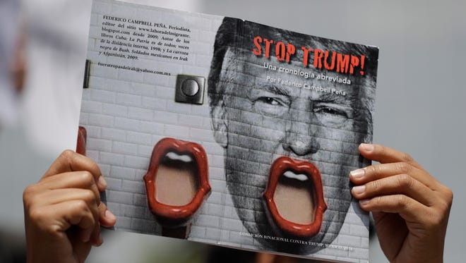 "In this Aug. 31, 2016 file photo, a demonstrator protesting Donald Trump's meeting with the Mexican president holds up a book jacket with the title; ""Stop Trump!"" during a morning protest at the Angel of Independence Monument in Mexico City. Now with Trump acting as Unites States President, Mexico is mobilizing to resist his policies in ways that range from the sensible to the strange."