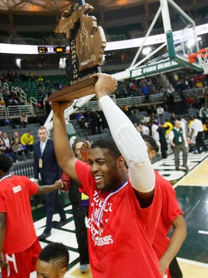 Flint Beecher's Aquavius Burks raises the Class C state championship trophy on March 28, 2015 in East Lansing.