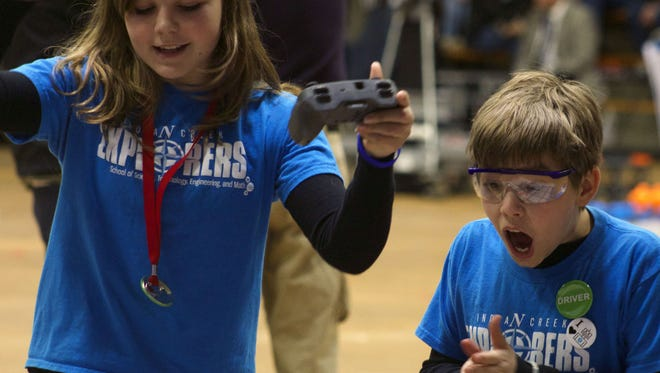 Ian Solenberg (right) cheers as he and his teammate finish a game during the Indianapolis VEX Robotics Championship on Jan. 8 at the University of Indianapolis. Ian, a fifth grader at Indian Creek Elementary, and his team advanced to the state championships.