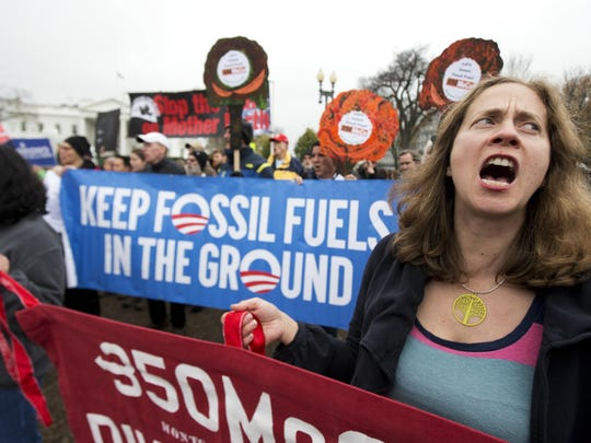 Kristin Cook, right, of Potomac, Md., joins a rally outside the White House last year in support of the climate talks in Paris. Seventy-one percent of the American public wants the federal government to do something about global warming, a new poll says.