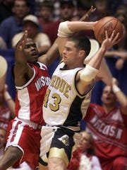 Carson Cunningham, during his playing days at Purdue, looks to pass against the stifling defense of Wisconsin's Travon Davis.