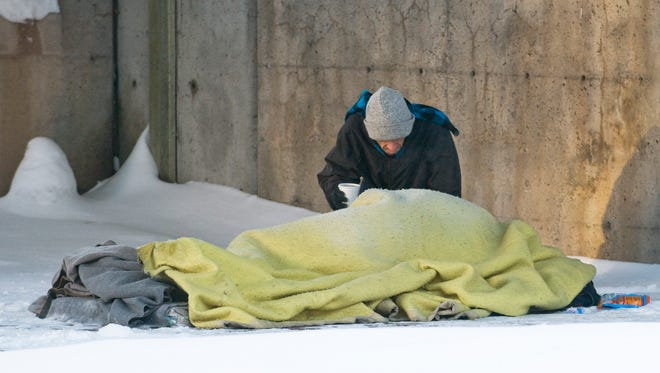 A man checks on a homeless person sleeping on a snow-covered sidewalk on Dec. 23, 2008, in Montreal, Quebec, Canada. A week after a homeless man was found dead in Park Viger, other homeless people were still sleeping outdoors in very cold conditions.