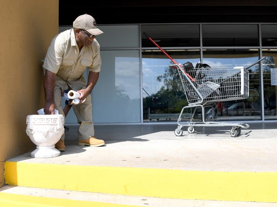 Paul Poore cleans out an ashtray at the Westgate Shopping Center on Wednesday, Aug. 30, 2017. Poore has been working at the shopping center for 57 years.