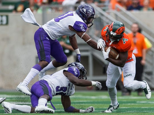 Colorado State running back Dalyn Dawkins, right, is stopped by Abilene Christian linebacker Landry Hutchins, lower left, and safety Brandon Richmond during the second half Saturday, Sept. 9, 2017, in Fort Collins, Colo. Colorado State won 38-10