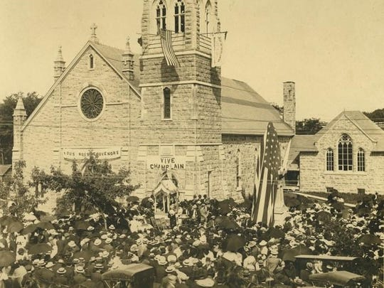 "Historic photo of St. Mary's Church in Champlain, N.Y. Samuel de Champlain is memorialized as the ""Father of New France"" and many places, streets, and structures in northeastern North America bear his name, or have monuments established in his memory. Some 6,000 visitors descended on Champlain for the dedication of the Champlain Monument on July 4, 1907, the first in the United States, outside St. Mary's Church. The entire village was decorated for the occasion with American flags and the tri-color of France."