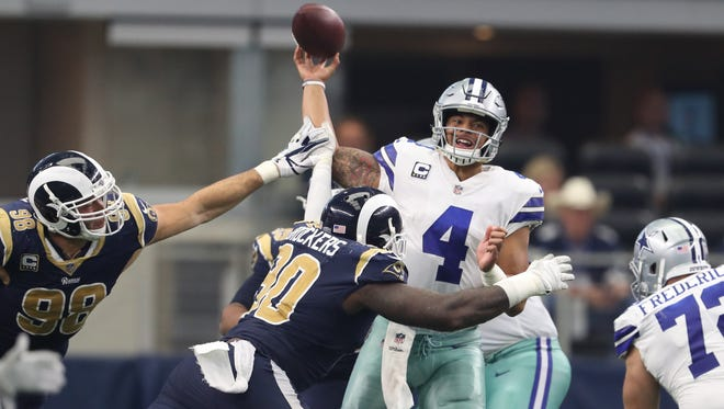 Dallas Cowboys quarterback Dak Prescott throws an interception as hhis arm is hit by Los Angeles Rams linebacker Connor Barwin in the fourth quarter at AT&T Stadium.