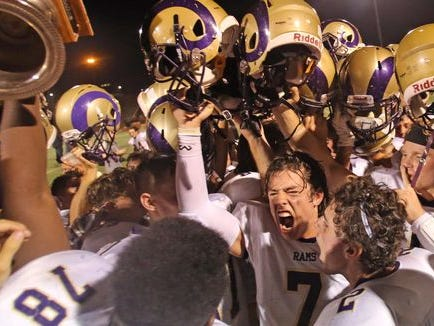 Clarkstown North celebrates their 26-8 win over Clarkstown South and winning Supervisor's Cup at Clarkstown South High School in West Nyack Sept. 4, 2015.