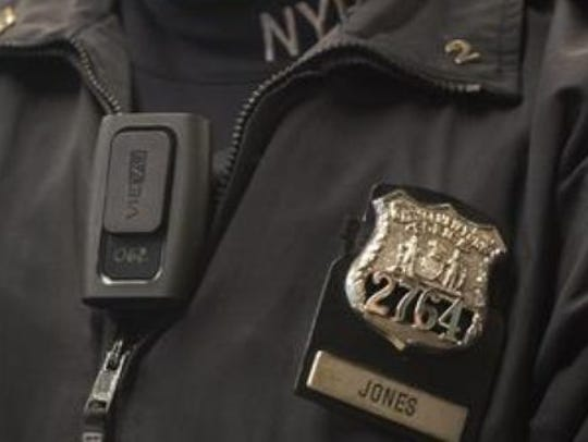 An officer models a version of body cameras.