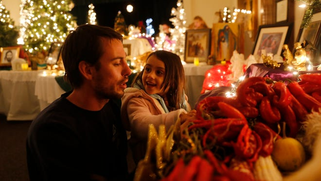 Scott Willard and his daughter, Camille Willard, look at a nativity scene Wednesday at the Bloomfield Stake Center of the Church of Jesus Christ of Latter-day Saints.