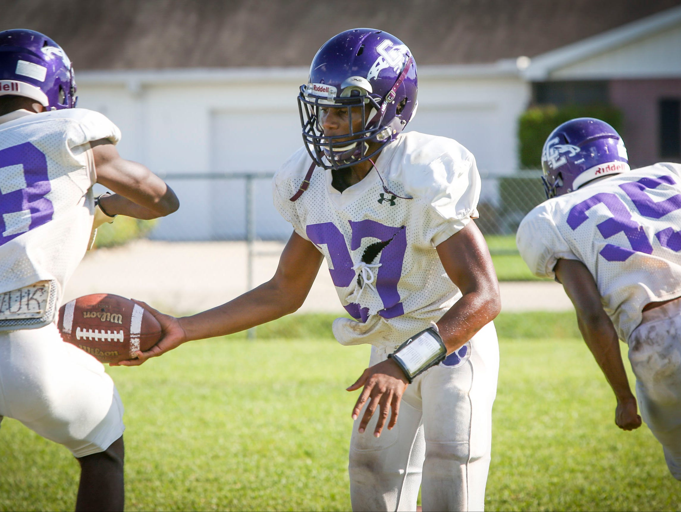 Trent Rogers, quarterback at Cypress Lake High School, hands off the ball to a teammate during football practice Wednesday afternoon.