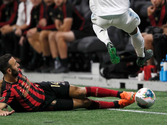 Atlanta United forward Justin Meram (14) slides to knock the ball away from a Minnesota United player during the first half of the U.S. Open Cup soccer match Tuesday, Aug. 27, 2019, in Atlanta. (AP Photo/John Bazemore)