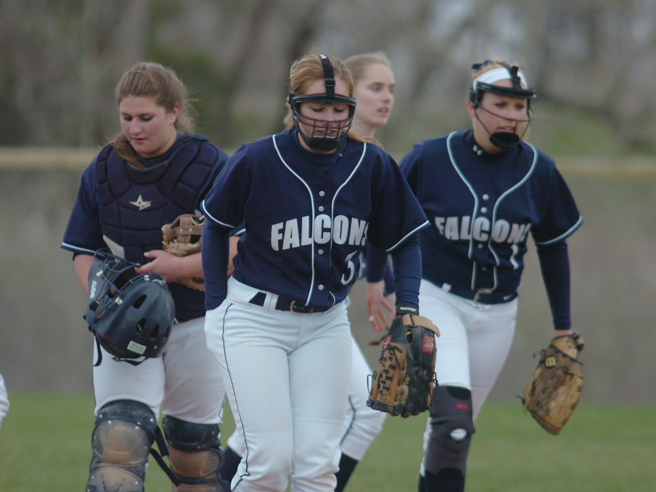 Farmington sophomore Danielle Petras (left) and senior infielders Alexa Flourre (center) and Alli Gambill leave the field at the end of a half inning.