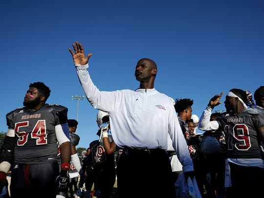 Lane College head coach Derrick Burroughs raises his arm as the team faces the marching band after their 19-18 victory over Benedict College at Lane Field in Jackson on Oct. 8, 2016.