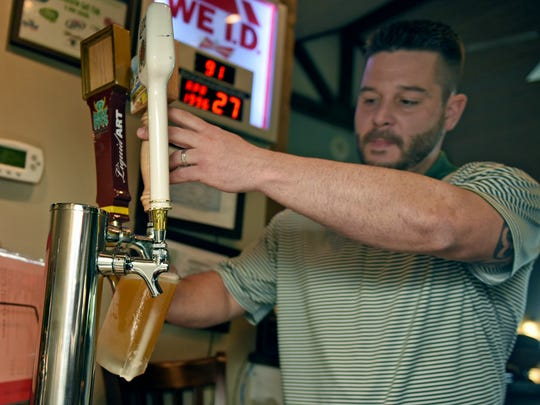 Mike Porter, manager at Greencastle Greens Golf Club, 2000 Castlegreen Drive, pours beer for customers on Thursday, April 27, 2017. The Antrim Township business is licensed to sell alcohol in an area that was formally  a dry township.