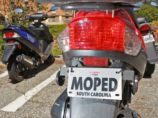 A registered moped in South Carolina has a sticker on a tag.