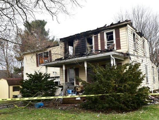 Caution tape surrounds a home in the aftermath of a