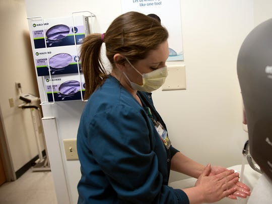 Kirsten Shoop, LPN, washes her hands while working in the emergency room Thursday, February 8, 2018 at Chambersburg Hospital. Mask and hand sanitizer are available for visitors during the flu season.