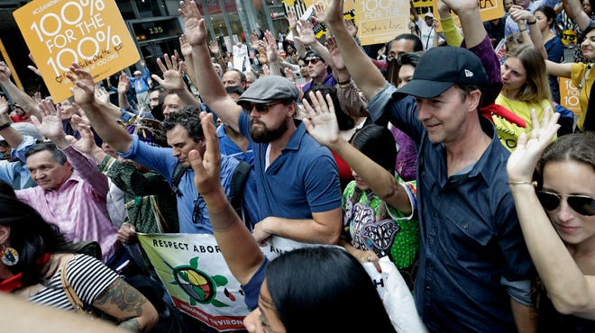 Actors Mark Ruffalo, left, Leonardo DiCaprio, center, and Edward Norton raise their hands during a moment of silence while participating in the People's Climate March in New York City on Sunday, Sept. 21.