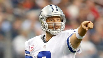 Dallas Cowboys quarterback Tony Romo (9) points to a defender in the game against the Houston Texans at AT&T Stadium.