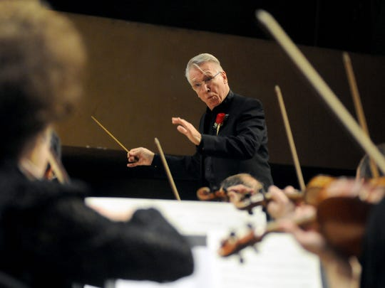 Principal conductor, Douglas Bianchi, conducts the orchestra during the national anthem Saturday, Feb 28, during a concert at McMorran Theatre.