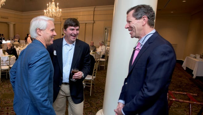 Ivan Maisel, senior writer for ESPN, right, vistas with Perry Hooper Jr., left, and Ben Venable, right, at the Montgomery Quarterback Club on Tuesday evening September 29, 2015 at the Montgomery Country Club in Montgomery Ala.