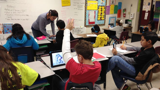 Students at Ramirez-Burks Elementary in Cotulla, Texas, navigate iPads to work on research papers, as teacher Cindy Ochoa answers questions. The school district, once one of the poorest in Texas, received an influx of cash thanks to the state oil boom.