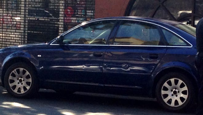 Bullet holes seen in the side of a blue Audi at the scene of shooting, which occurred in Mount Vernon on East Third Street between South First and South Second avenues Tuesday morning.