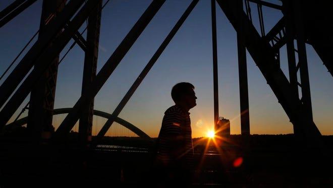 Jack Mitchell walks to work Wednesday morning on the Purple People Bridge.