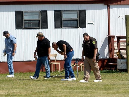 Law enforcement investigators walk the property at