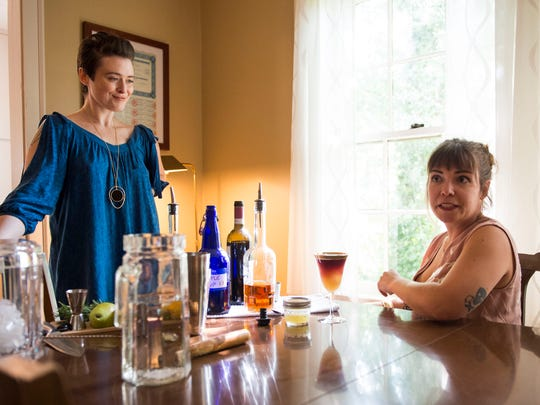Amanda Mohney, left, and Casey Fox sit in Fox's home while demonstrating cocktail mixing services their business Libacious offers. Libacious offers mobile craft cocktail catering and is owned by Fox, Jesse Fox Mayshark and Mohney.