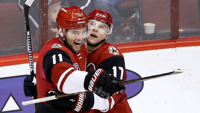 Arizona Coyotes center Martin Hanzal (11) smiles as he celebrates his game-winning goal against the San Jose Sharks with right wing Radim Vrbata (17) during overtime of an NHL hockey game Saturday, Nov. 19, in Glendale. The Coyotes defeated the Sharks 3-2.