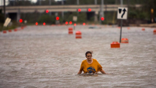 A woman who identified herself as Valerie walks along flooded President Street after leaving her homeless camp after Hurricane Matthew caused flooding, Saturday, Oct. 8, 2016, in Savannah, Ga.  Matthew plowed north along the Atlantic coast, flooding towns and gouging out roads in its path. (AP Photo/Stephen B. Morton)