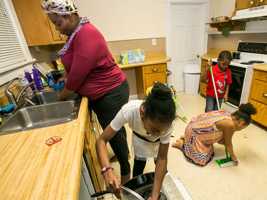 Crystal Henderson and her children, from left, Callie, Camile and Christian, clean up the kitchen in their new home. They were previously homeless.