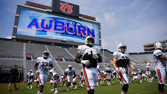 Auburn players run out to Jordan-Hare Stadium field for first scrimmage action Monday. This scrimmage marked the first time the Tigers played under new video board.
