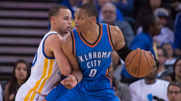 January 5, 2015; Oakland, CA, USA; Oklahoma City Thunder guard Russell Westbrook (0) dribbles the basketball against Golden State Warriors guard Stephen Curry (30, left) during the third quarter at Oracle Arena.