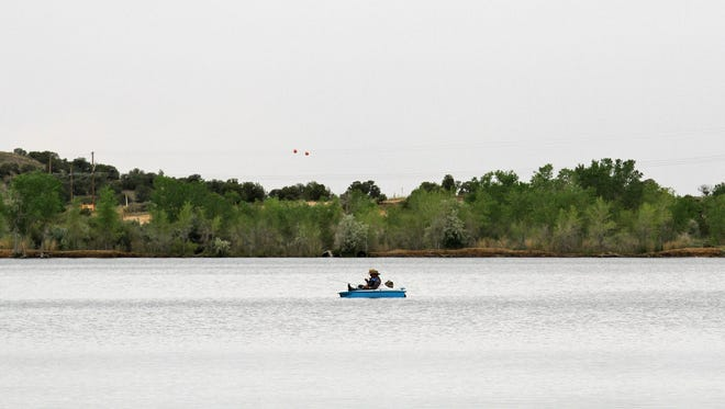 Anglers fish from a paddle boat June 5, 2015, at Farmington Lake. The lake opens for swimming later this month.
