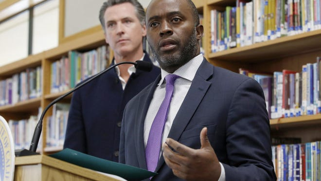 In this Oct. 31, 2019, file photo, state Superintendent of Public Instruction Tony Thurmond answers a reporter's question during a visit with California Gov. Gavin Newsom, background, to Blue Oak Elementary School in Cameron Park, Calif.
