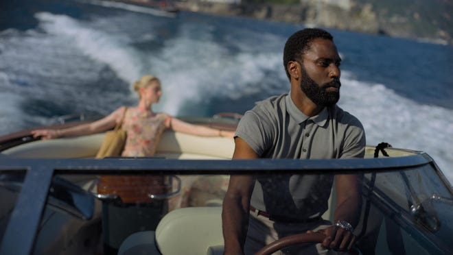 "This image released by Warner Bros. Entertainment shows Elizabeth Debicki, left, and John David Washington in a scene from ""Tenet."""