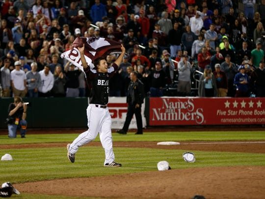Missouri State's Matt Hall runs toward teammates with a MSU flag after they beat the Iowa Hawkeyes during the 6th game of the NCAA Division I Baseball Regional in Springfield, Mo. on Sunday, May 31, 2015.