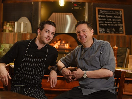 Andrew Bazzini, left, and his father, Paul, the executive chef at the Hearth & Tap Co. in Montvale. The pair bring divergent but complementary old-school and new-school techniques to the restaurant's kitchen.