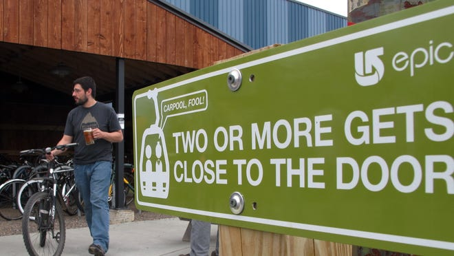 """""""Carpool, fool!"""" — a sign at Burton Snowboards encourages shared rides through choice parking spots in this file photo from 2014. Employees who bicycle park in the even-closer """"Wheel House,"""" pictured in the background."""