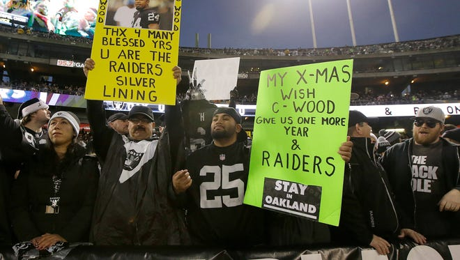 Fans hold up signs for retiring Oakland Raiders cornerback Charles Woodson and for the Raiders to stay in Oakland during the first half of an NFL football game between the Raiders and the San Diego Chargers in Oakland, Calif., on Thursday.