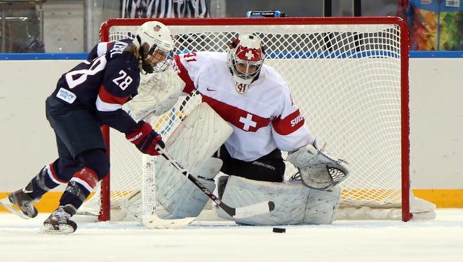 USA forward Amanda Kessel attempts a shot against Switzerland goalkeeper Florence Schelling.